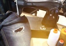 古色古香的缝纫机和蓝色牛仔裤 免版税图库摄影