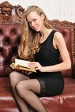 古色古香的美丽的白肤金发的书读取沙发 免版税库存图片