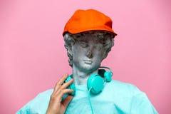 古色古香的胸象男性在有耳机的盖帽在桃红色背景 免版税图库摄影