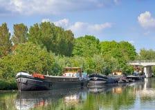 古色古香的船在有豪华的绿色植被的,提耳堡大学,荷兰Pius港口停泊了 图库摄影
