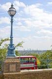 古色古香的街灯和红色伦敦公共汽车 免版税库存图片