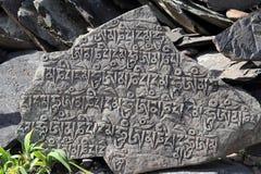 古色古香的西藏字母表被雕刻的石头 免版税库存图片