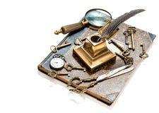 古色古香的钥匙,怀表,墨水笔,寸镜,书 免版税库存照片