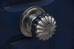 古色古香的银色门把-被擦亮对亮光在使用年限之前在一个蓝色门登上了 库存照片