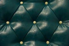 古色古香的绿色皮革和按钮沙发 免版税库存图片
