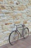 古董或减速火箭的被氧化的自行车外面在一个石墙上 图库摄影
