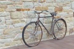 古董或减速火箭的被氧化的自行车外面在一个石墙上 免版税图库摄影