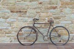 古董或减速火箭的被氧化的自行车外面在一个石墙上 免版税库存照片