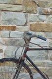 古董或减速火箭的被氧化的自行车外面在一个石墙上 库存图片