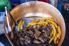古铜色罐,用油煎的猪肉和香蕉 免版税库存照片