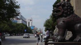 古铜色金属石头狮子在古城门,都市镇繁忙的公路交通前面的独角兽&瓷石曲拱 股票视频