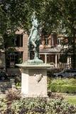 古铜色雕象密室乔安娜D弧-圣贞德战争纪念建筑在一个五颜六色的庭院里在一个晴天 库存照片