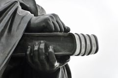 古铜色雕象细节:拿着书的两只手 库存照片
