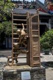 古铜色雕象,儿童在门道入口的` s比赛 免版税库存图片