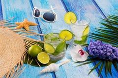 古巴人在热带蓝色木花和海星的Mojito鸡尾酒 图库摄影