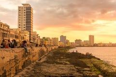 古巴人坐Malecon防波堤在日落 库存图片