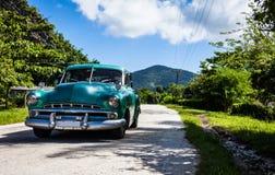 古巴加勒比经典汽车在街道上drived在山脉马埃斯特腊山 库存图片