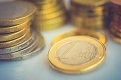 另外价值被堆积的新的发光的白色和金黄欧洲硬币在被定调子的桌面财务投资股票储款概念的 免版税图库摄影
