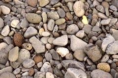 另外大小和形状小卵石的顶视图灰色和棕色 库存照片