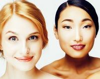 另外妇女:亚洲人,在白色背景愉快微笑一起隔绝的白种人,皮肤的不同的类型,生活方式 免版税库存照片