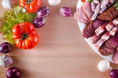 另外开胃菜框架在板材的喜欢jamon,烟肉,用不同的菜的蒜味咸腊肠 库存图片