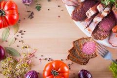 另外开胃菜框架,象jamon、烟肉、蒜味咸腊肠和面包片用不同的菜的 蒜味咸腊肠片断在叉子的 库存图片