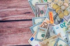 另外欧元和美元与硬币在书桌上 免版税库存照片