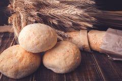 另外种类在一张土气木桌上的新近地被烘烤的面包在麦子附近 概念吃健康 关闭 库存图片