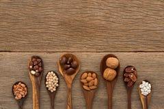 另外种类豆和扁豆在木匙子在木头后面 免版税库存照片