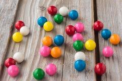 另外色的泡泡糖在老土气木背景驱散了 免版税库存图片