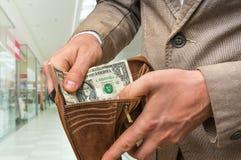 只供以人员拿着有里面一美元的皮革钱包 免版税库存照片
