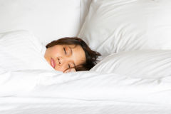 只显示面孔妇女在白色毯子在床上的被卷起的睡眠 免版税库存图片