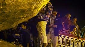 只有男性人民胶合了小金币到神圣的摇滚的Kyaiktiyo塔 免版税库存照片