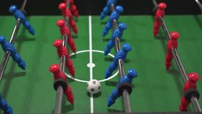 叫作橄榄球喷射器比赛的桌足球,蓝色和红色球员的Foosball 股票录像