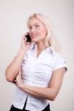 叫可爱的金发碧眼的女人移动电话 免版税库存图片