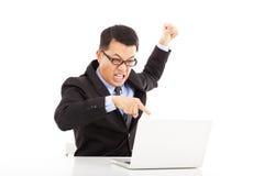 叫喊的商人和做有膝上型计算机的一个拳头 库存图片