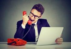 叫恼怒的年轻的商人与膝上型计算机失败的顾客服务尖叫在电话 免版税库存图片