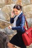 叫愉快的妇女赶紧的旅行的皮箱电话 免版税库存图片
