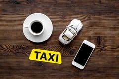 叫有流动app的一辆出租汽车和咖啡木桌背景顶视图copyspace 免版税库存照片