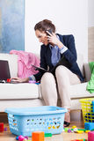叫的妇女做家事和手机同一时间 库存照片