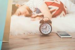 叫醒和关闭闹钟的愉快的年轻亚裔妇女 免版税库存图片