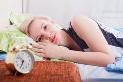 叫醒在家在床上的微笑的年轻白肤金发的妇女在明亮的卧室,早晨概念 在前面弄脏的时钟 图库摄影