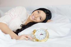 叫醒在床上的美丽的深色的少妇蓝眼睛女孩拿着闹钟愉快的微笑的&看的照相机 免版税库存照片