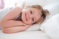 叫醒微笑的愉快的女孩女儿看在父母` s床上的照相机对早晨 愉快的轻松的家庭生活与 免版税库存图片