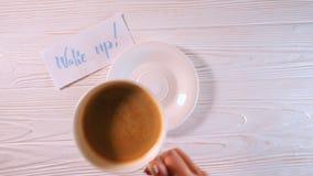 叫醒文本 字法词字体在白皮书的与由书法家的蓝墨水 女性手采取咖啡从 股票录像