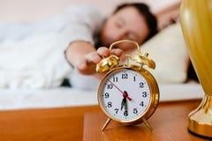 6 30叫醒电话:拉扯手的年轻深色的男人或妇女床对在前景的闹钟 免版税库存图片