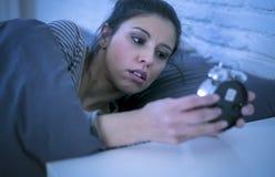 叫醒翻倒的年轻美丽和懊恼拉丁妇女对感到闹钟清早懒惰起来或suffe的声音 免版税库存照片