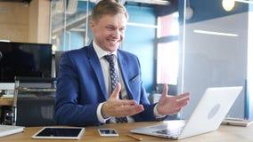 召开网上会议的确信和可爱的商人在他的办公室 免版税库存图片