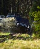 召集,竞争和四轮驱动的概念 与土飞溅的越野车或SUV横穿水坑 图库摄影