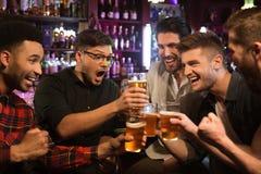 叮当响与啤酒杯的愉快的男性朋友在客栈 免版税图库摄影